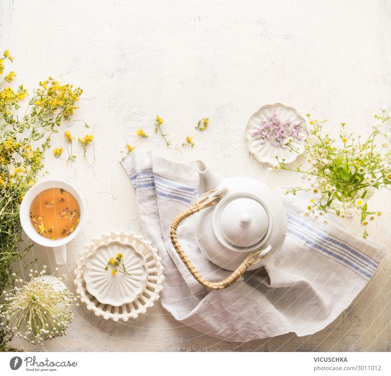 Herbal tea setting with fresh medical herbs , teapot and cup of tea. Saint-John's-wort herbs and flowers on white table background, top view. Herbal medicine. Natural dietary supplement