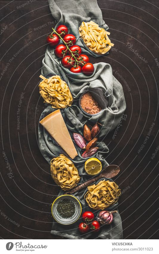 Tuna pasta cooking ingredients on dark rustic background, top view. Grocery products of Italian cuisine. Italian food. Caned tuna. Vertical. Flat lay grocery