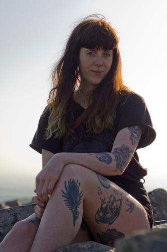 Carina - Young tattooed woman sits on a mountain Woman Tattooed Summer T-shirt Mountain Above Human being Exterior shot Young woman Nature evening light Sit