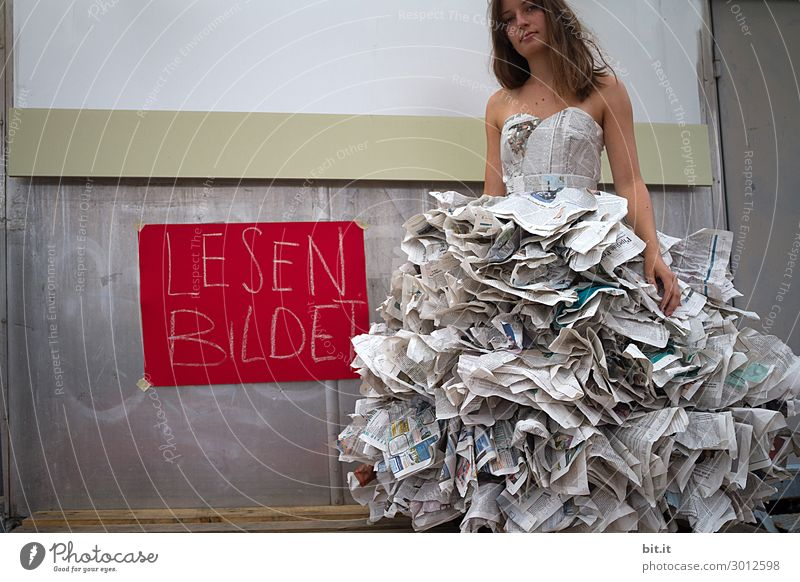Young woman in a newspaper dress, invited to read. Feminine Youth (Young adults) Adults Art Work of art Theatre Stage Youth culture Media Print media Newspaper