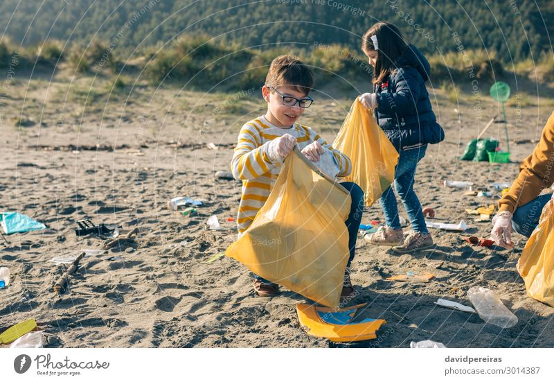 Children volunteers cleaning the beach Woman Human being Man Beach Adults Environment Family & Relations Happy Boy (child) Work and employment Sand Dirty