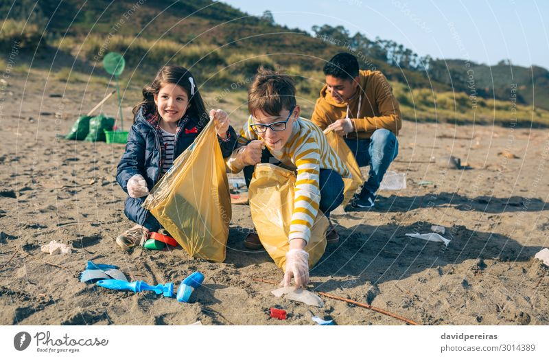 Young volunteers cleaning the beach Happy Camping Beach Child Work and employment Human being Boy (child) Woman Adults Man Group Sand Plastic Smiling Dirty