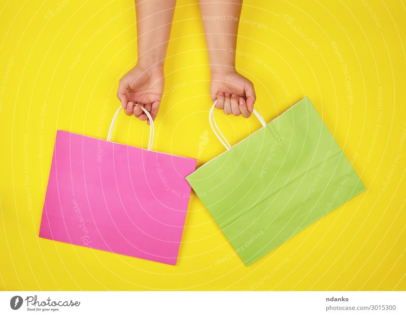 two hands holding paper shopping bags Colour Green Hand Lifestyle Yellow Style Business Fashion Pink Design Modern Creativity Gift Shopping Paper To hold on