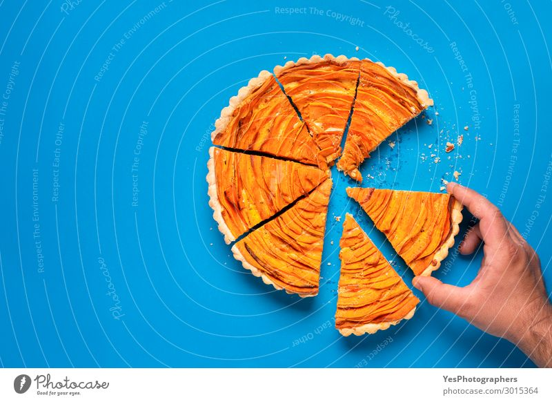 Man hand taking a slice of sweet potato tart Eating Decoration Hand Autumn Tradition Thanksgiving day above view American Blue background Crumbs Crust Cut Dish