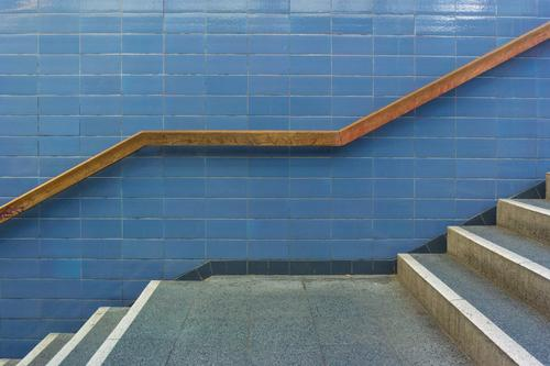 Stair landing with wooden handrail and tiled wall Manmade structures built Stairs Exploit Handrail Banister Tile Stone Architecture Downward Upward Movement