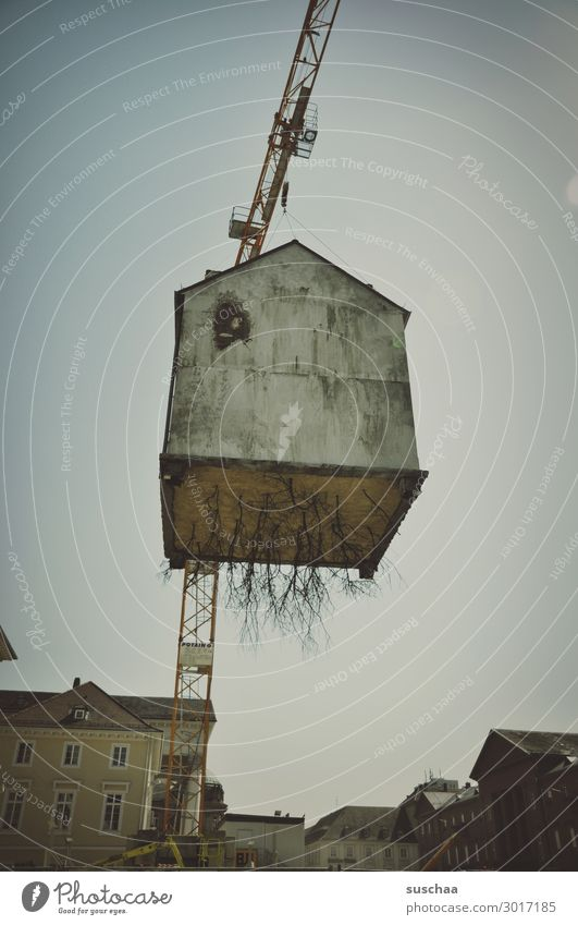 Airy house in the air. House (Residential Structure) Crane Height Town Surrealism Building Hover Tall Run away roots Dismantling Transport Exceptional