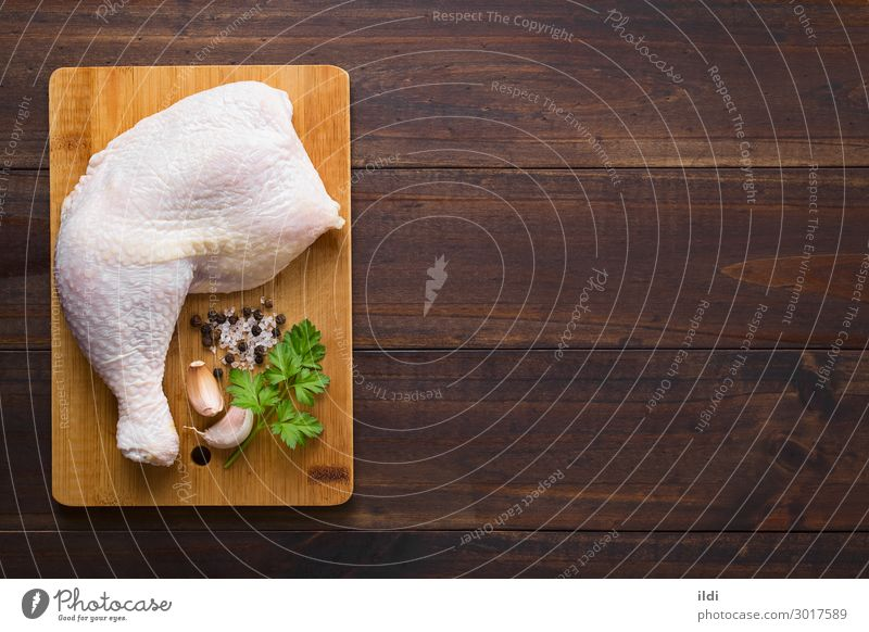 Raw Chicken Thigh Meat Fresh food poultry cooking leg part Protein board cutting wood seasoning salt pepper Garlic Parsley Copy Space Top overhead Horizontal