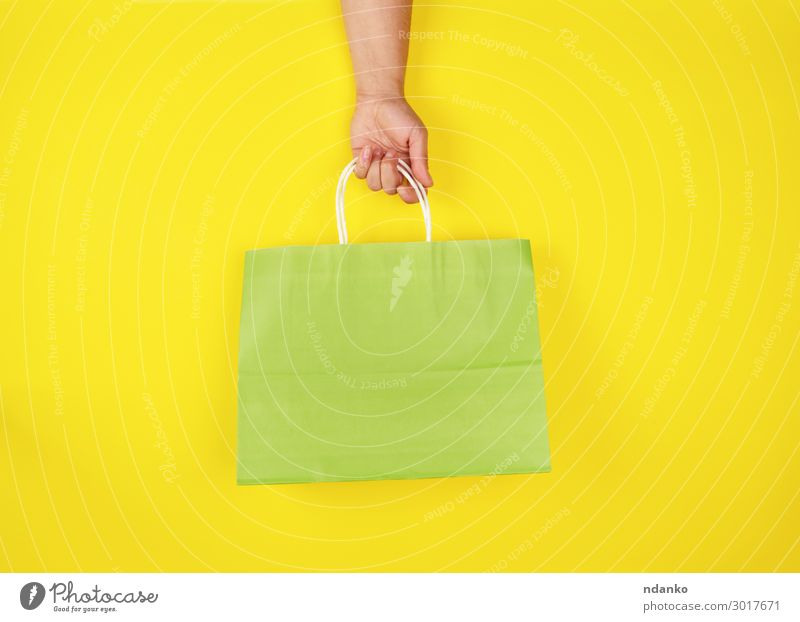 female hand holding a green paper shopping bag Woman Human being Green Hand Lifestyle Adults Yellow Style Business Fashion Design Modern Creativity Gift