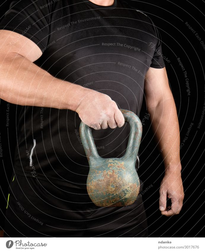 strong athlete in black clothes holding an iron kettlebell Lifestyle Sports Human being Man Adults Arm Hand Fingers 1 30 - 45 years Fitness Stand Athletic Dark