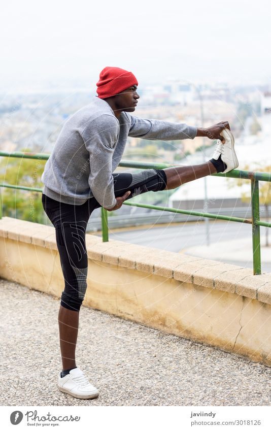 Black man doing stretching before running in urban background Lifestyle Body Winter Sports Jogging Human being Masculine Young man Youth (Young adults) Man