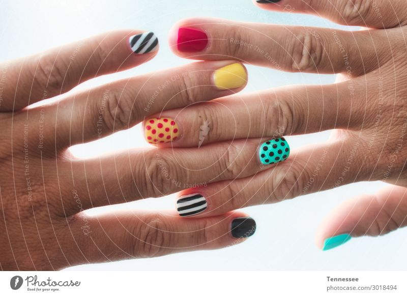 A pair of female hands with colored painted nails Fingernail polish Painted Paints and varnish Pattern Multicoloured Colour Design Exceptional Medical treatment