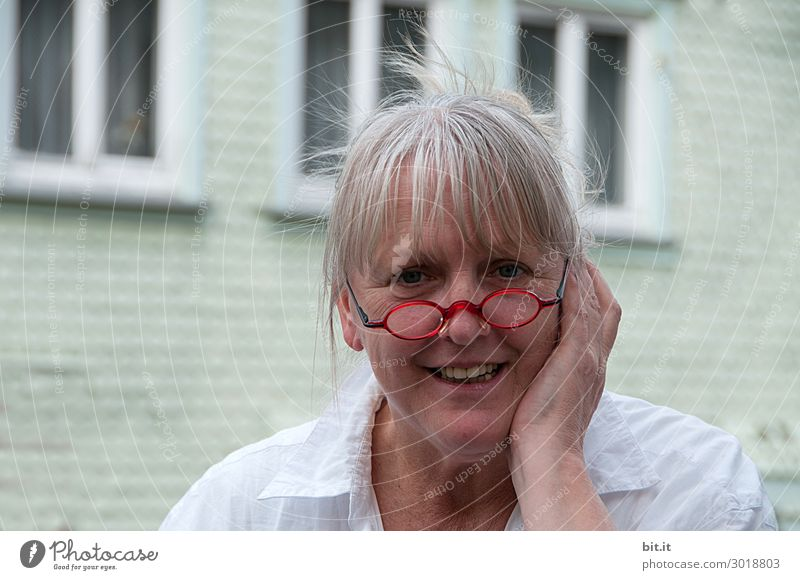 Mature woman with red glasses on her nose, bangs, grey hair, stands in front of a white house with windows. Female senior, with pain in ear or tooth, holds hand protectively against cheek of face. Lady with a pleased, surprised expression.