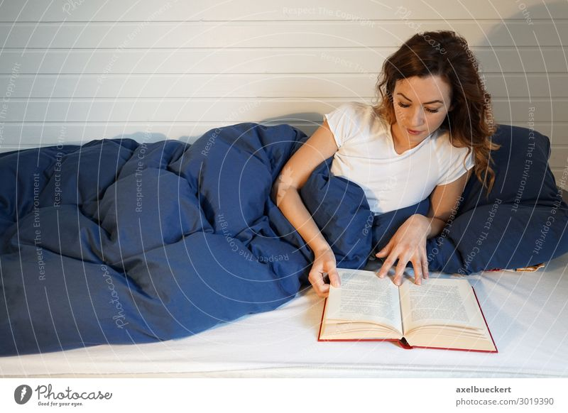 young woman reads a book in bed Lifestyle Relaxation Leisure and hobbies Living or residing Flat (apartment) Bed Bedroom Entertainment Human being Feminine