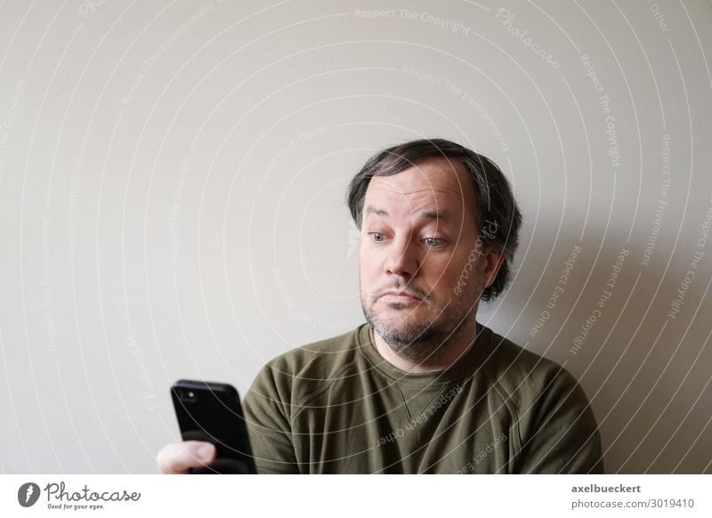 Man looks puzzled at smartphone Lifestyle Telephone Cellphone PDA Technology Entertainment electronics Telecommunications Internet Human being Adults 1