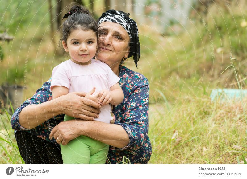 Senor grandmother embraced her little grandchild at field Woman Child Human being Vacation & Travel Nature Old Blue Green Landscape Loneliness Calm Joy Girl