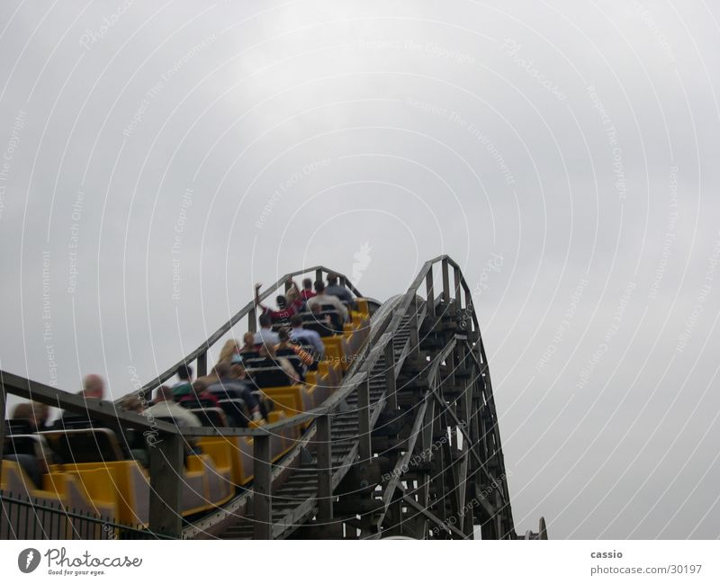 Ride up. Roller coaster Amusement Park Soltau Driving heath park Sky Human being Upward Bright background Copy Space top Clouds in the sky Cloud cover Skyward