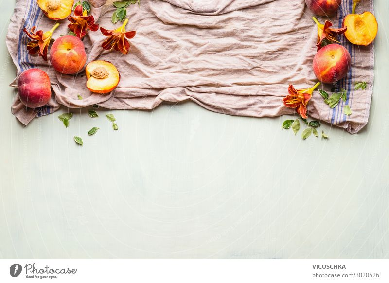 Food background with fresh whole and half peaches on kitchen towel with leaves, flowers and copy space for your design or product , top view. Flat lay. Horizontal. Border