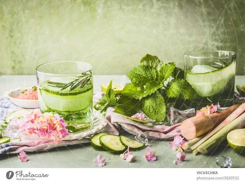Classes with cucumber lemonade or detox infused water and ice cubes on table with ingredients. Green color summer refreshing drinks preparation classes green