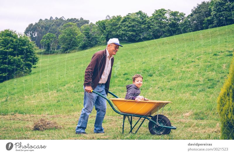 Senior man raking hay with pitchfork on field Lifestyle Joy Happy Leisure and hobbies Playing Summer Garden Child Gardening Human being Boy (child) Man Adults