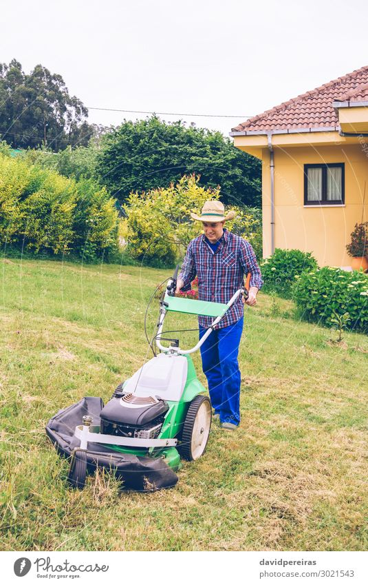 Young man mowing the lawn with lawnmower Summer House (Residential Structure) Garden Work and employment Profession Gardening Tool Engines Technology