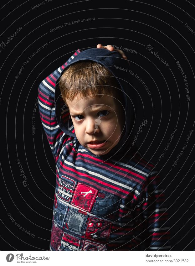 Angry boy with hoodie standing over black background Face Child Human being Boy (child) Man Adults Infancy Stand Sadness Authentic Dark Small Cute Crazy Anger