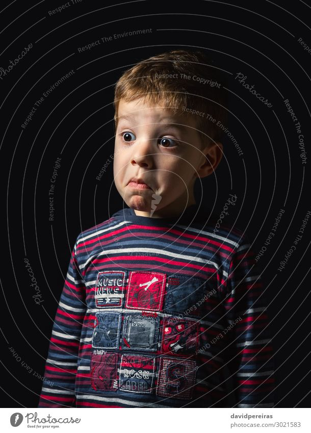 Confused boy with doubt face over black background Face Child Human being Boy (child) Man Adults Infancy Shirt Stripe Think Stand Authentic Dark Small Cute Red