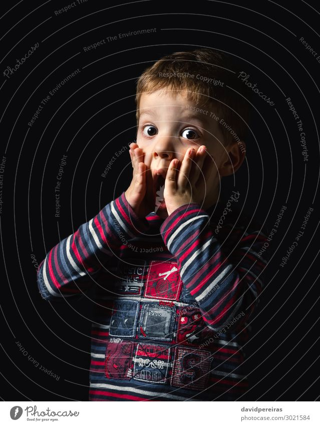 Surprised boy standing over black background Joy Happy Face Child Human being Boy (child) Man Adults Infancy Mouth Arm Hand Stripe Stand Authentic Dark Small