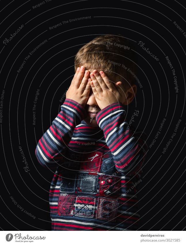 Scared boy covering his eyes over black background Face Child Human being Boy (child) Man Adults Infancy Hand Stripe Stand Cry Authentic Dark Small Cute Black