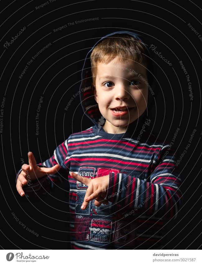 Happy boy with hoodie standing over black background Joy Face Child Schoolchild Human being Boy (child) Man Adults Infancy Hand Fingers Clothing Shirt Stripe