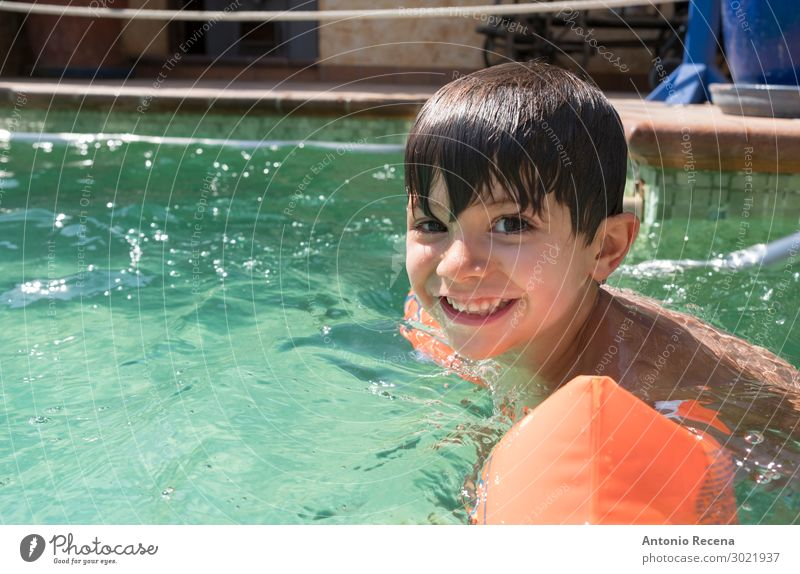 Boy wearing arm floaties in a swimming pool Joy Happy Swimming pool Leisure and hobbies Child Human being Boy (child) Man Adults Infancy Arm Brunette Smiling