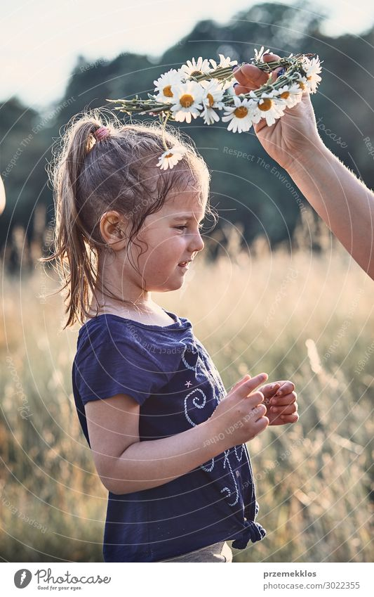 Mother putting a coronet of wild flowers on a head of girl Child Human being Vacation & Travel Nature Summer Green Landscape Hand Flower Relaxation Joy Girl