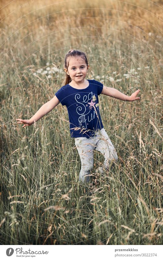 Little happy smiling girl playing in a tall grass Lifestyle Joy Happy Relaxation Vacation & Travel Summer Child Human being Girl 1 3 - 8 years Infancy