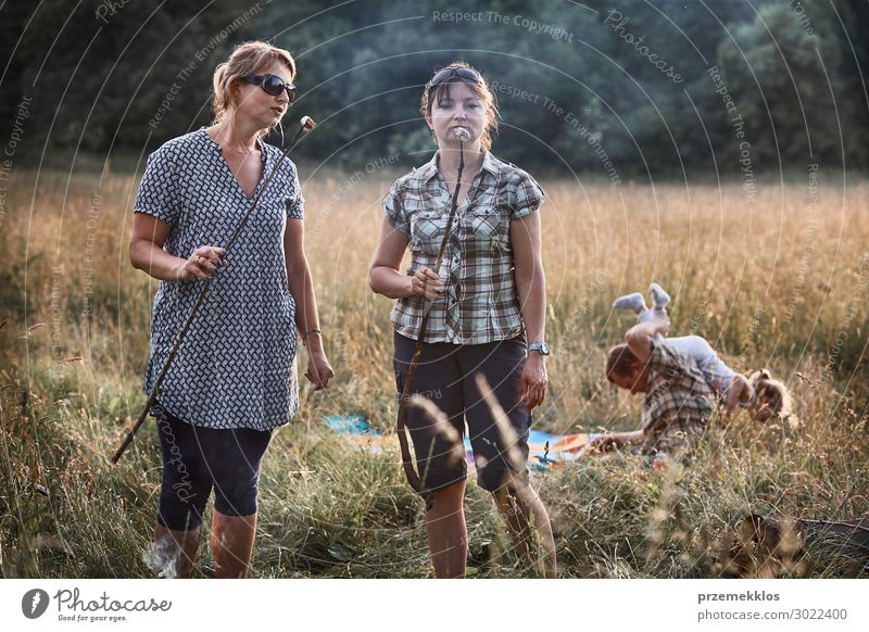 Women roasting a marshmallows over a campfire Lifestyle Joy Happy Relaxation Leisure and hobbies Playing Vacation & Travel Summer Summer vacation Child