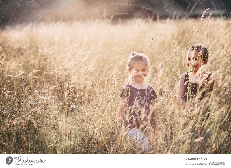 Little happy smiling kids playing in a tall grass Lifestyle Joy Happy Relaxation Vacation & Travel Summer Summer vacation Child Human being Girl Boy (child) Man