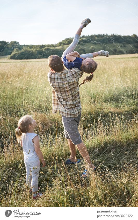 Father tossing little girl in the air Woman Child Human being Vacation & Travel Nature Man Summer Green Landscape Relaxation Joy Girl Lifestyle Adults