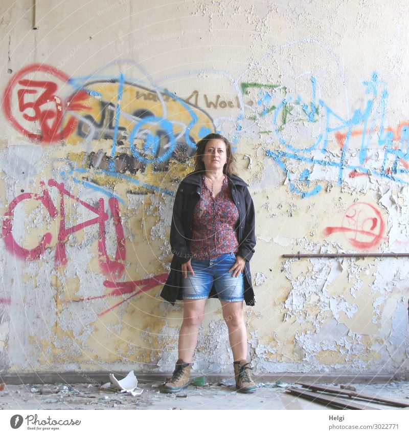 Portrait of a woman with short jeans, colourful blouse and dark jacket standing in front of a ramshackle wall with graffiti Human being Feminine Woman Adults 1