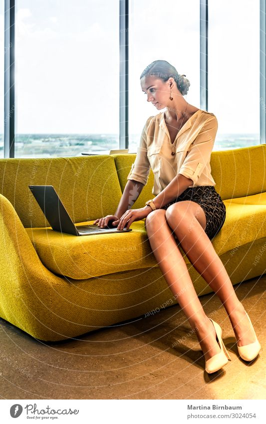 Young woman using a laptop at home on a couch Woman Human being Beautiful White Adults Happy Business Work and employment Office Modern Technology Smiling Sit
