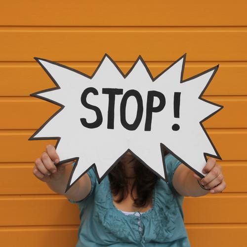 Stop sign held by a woman in front of an orange wall Hand 1 Human being 30 - 45 years Adults Facade Clothing Shirt Brunette Long-haired Characters Signage