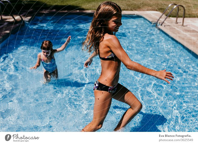 two beautiful sister kids at the pool playing. Summertime Child Human being Vacation & Travel Youth (Young adults) Young woman Blue Beautiful Sun Joy Girl