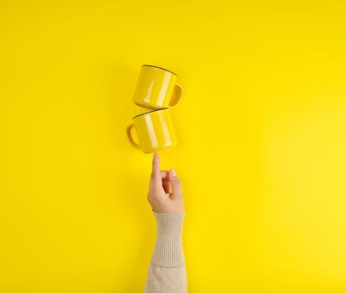 two yellow ceramic cups are supported by a female hand Breakfast Coffee Tea Cup Kitchen Arm Hand Fingers Hot Bright Clean Yellow Colour Hold background Blank
