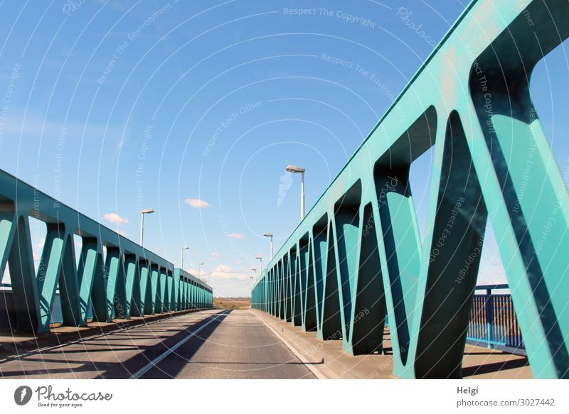 Road with turquoise metal construction of the Peene bridge near Anklam in front of a blue sky Environment Bridge Manmade structures Architecture