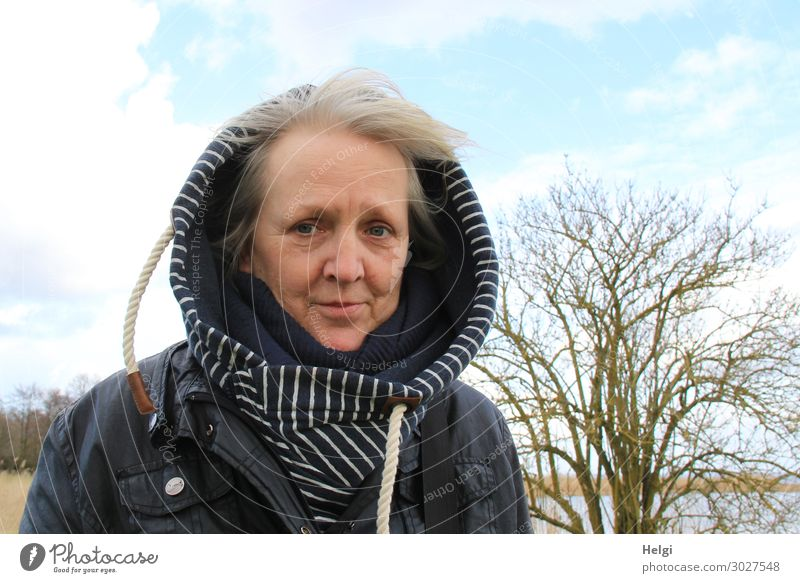 Senior with hooded jacket stands outside in the wind when the weather is fine Human being Feminine Woman Adults Female senior Senior citizen 1