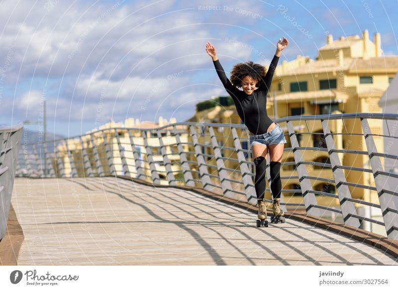 Black woman, afro hairstyle, on roller skates riding outdoors on urban bridge with open arms. Lifestyle Joy Happy Beautiful Hair and hairstyles