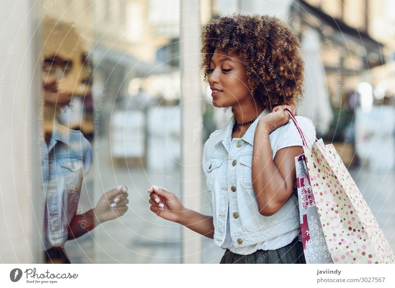 Young black woman in front of a shop window in a shopping street. Lifestyle Shopping Style Happy Beautiful Hair and hairstyles Human being Feminine Young woman