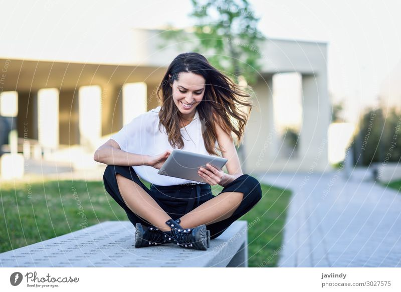 Young woman using digital tablet sitting outdoors in urban background. Lifestyle Happy Beautiful Reading Academic studies Work and employment Profession