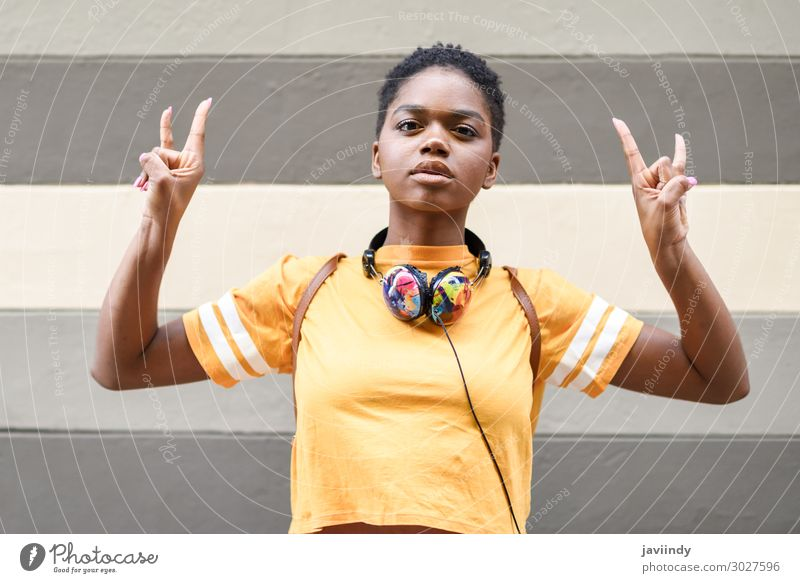 Black woman making the gesture of the horns Style Hair and hairstyles Face Music Headset Human being Feminine Young woman Youth (Young adults) Woman Adults Hand