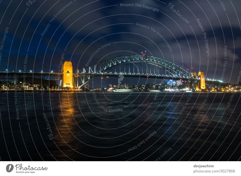 Sydney Bridge at night . In the foreground the sea. In the back of the picture the illuminated bridge with yellow illuminated pillars. Trip Summer Ocean Water