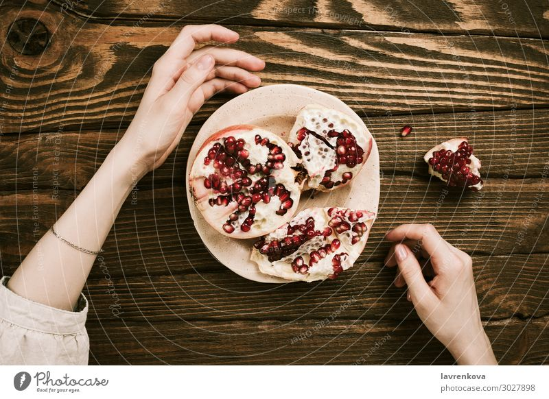 woman's hands and a plate with pomegranate on wooden table Wood Table Vegetarian diet Organic Sweet Healthy Healthy Eating Woman flat lay Food Fruit Hand