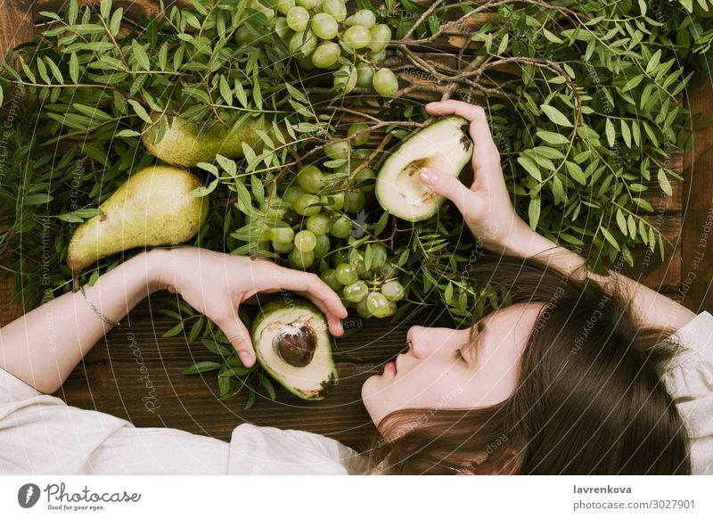 woman lying on wooden table holding grapes, pears and avocados Agriculture Avocado Branch Farm Woman flat lay Food Healthy Eating Food photograph Fresh Fruit