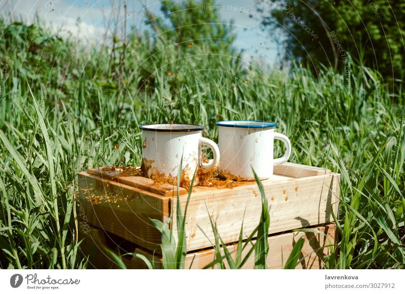 enamel mugs with coffee or tea on a wooden box Spring Grass Tea Exterior shot Beverage Drinking Wood Splashing Hot Cup Enamel Coffee Picnic Hiking Summer Nature